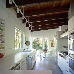 ブリッジポートの中サイズのモダンスタイルのおしゃれなキッチン (ダブルシンク、フラットパネル扉のキャビネット、白いキャビネット、クオーツストーンカウンター、シルバーの調理設備の、セラミックタイルの床、アイランドなし) の写真