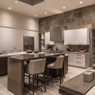 This is an example of an expansive contemporary u-shaped open plan kitchen in Phoenix with an undermount sink, flat-panel cabinets, white cabinets, quartz benchtops, slate splashback, stainless steel appliances, light hardwood floors, multiple islands, beige floor and grey benchtop.
