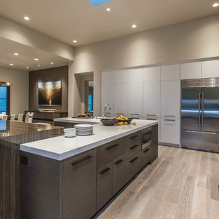Design ideas for a contemporary u-shaped open plan kitchen in Phoenix with flat-panel cabinets, white cabinets, quartz benchtops, green splashback, slate splashback, stainless steel appliances, light hardwood floors, multiple islands, beige floor and white benchtop.