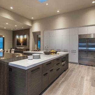 Offene Moderne Küche in U-Form mit flächenbündigen Schrankfronten, weißen Schränken, Quarzwerkstein-Arbeitsplatte, Küchenrückwand in Grün, Rückwand aus Schiefer, Küchengeräten aus Edelstahl, hellem Holzboden, zwei Kücheninseln, beigem Boden und weißer Arbeitsplatte in Phoenix