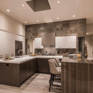 Design ideas for an expansive contemporary u-shaped open plan kitchen in Phoenix with an undermount sink, flat-panel cabinets, white cabinets, quartz benchtops, green splashback, slate splashback, stainless steel appliances, light hardwood floors, multiple islands, beige floor and white benchtop.