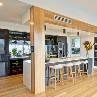 Inspiration for a contemporary l-shaped kitchen in Other with an undermount sink, flat-panel cabinets, grey cabinets, mirror splashback, stainless steel appliances, light hardwood floors, with island, brown floor and white benchtop.