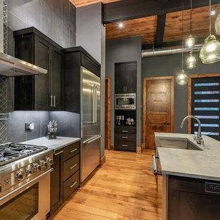 アトランタのラスティックスタイルのおしゃれなキッチン (エプロンフロントシンク、シェーカースタイル扉のキャビネット、黒いキャビネット、コンクリートカウンター、黒いキッチンパネル、セラミックタイルのキッチンパネル、シルバーの調理設備、無垢フローリング、茶色い床、グレーのキッチンカウンター) の写真