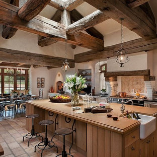 This is an example of an eat-in kitchen in Phoenix with a farmhouse sink, medium wood cabinets, beige splashback, black appliances and open cabinets.