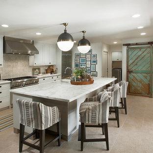 На фото: параллельная кухня среднего размера в стиле кантри с врезной раковиной, плоскими фасадами, белыми фасадами, мраморной столешницей, белым фартуком, техникой из нержавеющей стали, полом из травертина и островом с