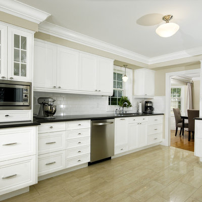 Kitchen - transitional kitchen idea in Toronto with glass-front cabinets, stainless steel appliances and subway tile backsplash