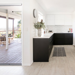 Beach style u-shaped kitchen in Sunshine Coast with an undermount sink, flat-panel cabinets, black cabinets, white splashback, subway tile splashback, stainless steel appliances, light hardwood floors, no island, beige floor and white benchtop.