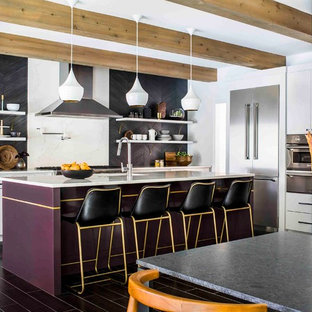 This is an example of a contemporary l-shaped eat-in kitchen in Atlanta with an undermount sink, flat-panel cabinets, purple cabinets, quartz benchtops, black splashback, stainless steel appliances, with island and black floor.