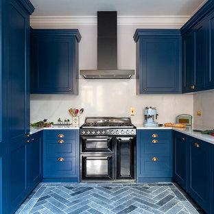 Mittelgroße Klassische Küche in U-Form mit Landhausspüle, Schrankfronten im Shaker-Stil, blauen Schränken, Marmor-Arbeitsplatte, Küchenrückwand in Weiß, Rückwand aus Marmor, schwarzen Elektrogeräten, Porzellan-Bodenfliesen, blauem Boden und weißer Arbeitsplatte in London