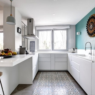 Inspiration for a scandinavian u-shaped kitchen in Tel Aviv with a drop-in sink, flat-panel cabinets, white cabinets, white splashback, panelled appliances, multi-coloured floor and white benchtop.
