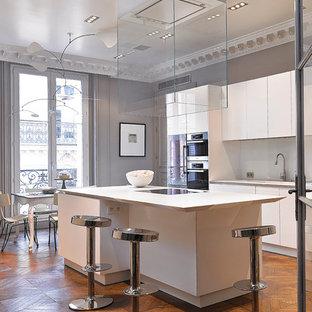 Réalisation d'une grande cuisine américaine parallèle design avec un îlot central, des portes de placard blanches et une crédence blanche.