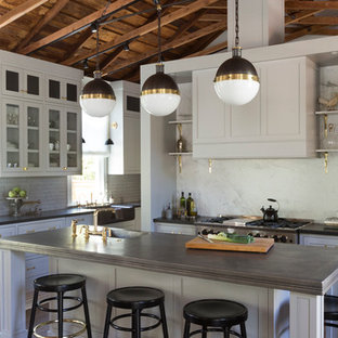 Mid-sized farmhouse eat-in kitchen ideas - Eat-in kitchen - mid-sized farmhouse u-shaped medium tone wood floor and brown floor eat-in kitchen idea in San Francisco with a drop-in sink, raised-panel cabinets, white cabinets, solid surface countertops, white backsplash, marble backsplash, stainless steel appliances and an island