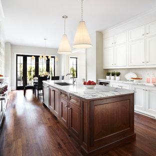Exempel på ett klassiskt kök, med en undermonterad diskho, luckor med infälld panel, vita skåp, mörkt trägolv och en köksö