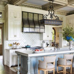 ミネアポリスのヴィクトリアン調のおしゃれなアイランドキッチン (落し込みパネル扉のキャビネット、ベージュのキャビネット、マルチカラーのキッチンパネル、無垢フローリング、マルチカラーのキッチンカウンター) の写真