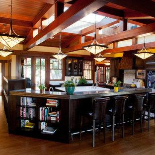 サンフランシスコの大きいエクレクティックスタイルのおしゃれなキッチン (シングルシンク、シェーカースタイル扉のキャビネット、茶色いキャビネット、亜鉛製カウンター、白いキッチンパネル、サブウェイタイルのキッチンパネル、パネルと同色の調理設備、濃色無垢フローリング) の写真