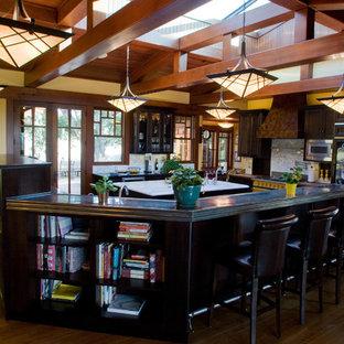 サンフランシスコの大きいエクレクティックスタイルのおしゃれなキッチン (亜鉛製カウンター、シングルシンク、シェーカースタイル扉のキャビネット、黒いキャビネット、白いキッチンパネル、サブウェイタイルのキッチンパネル、パネルと同色の調理設備、濃色無垢フローリング) の写真