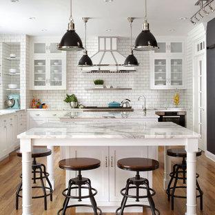 Große Klassische Küche in L-Form mit weißen Schränken, Marmor-Arbeitsplatte, Küchenrückwand in Weiß, Rückwand aus Metrofliesen, Küchengeräten aus Edelstahl, weißer Arbeitsplatte, zwei Kücheninseln, Unterbauwaschbecken, Glasfronten und braunem Holzboden in New York