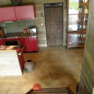 Offene, Zweizeilige, Mittelgroße Tropenstil Küche mit Doppelwaschbecken, Schrankfronten mit vertiefter Füllung, roten Schränken, Edelstahl-Arbeitsplatte, Küchenrückwand in Weiß, Glasrückwand, Küchengeräten aus Edelstahl, Betonboden, Kücheninsel, grauem Boden und grauer Arbeitsplatte in Sonstige