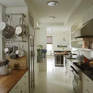 Photo of a modern galley separate kitchen in New York with wood benchtops, a farmhouse sink, open cabinets, white cabinets, stainless steel appliances and white floor.