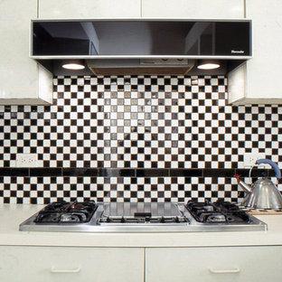 ニューヨークの広いモダンスタイルのおしゃれなキッチン (ドロップインシンク、フラットパネル扉のキャビネット、白いキャビネット、ラミネートカウンター、黒いキッチンパネル、セラミックタイルのキッチンパネル、黒い調理設備、セラミックタイルの床、白い床) の写真