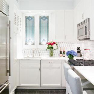 ニューヨークの小さいヴィクトリアン調のおしゃれなキッチン (アンダーカウンターシンク、シェーカースタイル扉のキャビネット、白いキャビネット、メタリックのキッチンパネル、シルバーの調理設備の、濃色無垢フローリング) の写真