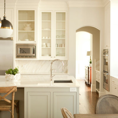 Eat-in kitchen - traditional eat-in kitchen idea in Dallas with glass-front cabinets, stainless steel appliances, white cabinets, white backsplash and stone slab backsplash