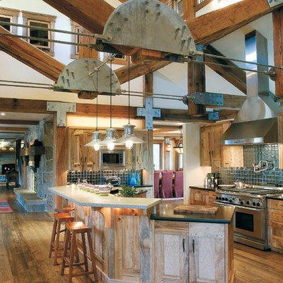 Example of a huge mountain style u-shaped medium tone wood floor open concept kitchen design in Salt Lake City with recessed-panel cabinets, blue backsplash, stainless steel appliances, granite countertops and two islands