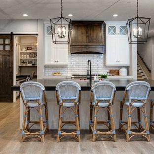 Immagine di una cucina country con lavello stile country, ante in stile shaker, ante bianche, paraspruzzi bianco, elettrodomestici in acciaio inossidabile, parquet chiaro e isola