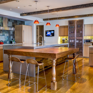 Eclectic kitchen in Los Angeles with flat-panel cabinets, light wood cabinets, metallic splashback, panelled appliances, medium hardwood floors, multiple islands and orange floor.