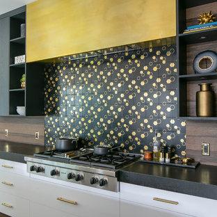 オレンジカウンティの広いコンテンポラリースタイルのおしゃれなアイランドキッチン (フラットパネル扉のキャビネット、黒いキャビネット、黒いキッチンパネル、無垢フローリング、茶色い床、黒いキッチンカウンター) の写真