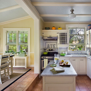 Traditional eat-in kitchen inspiration - Example of a classic eat-in kitchen design in New York with a drop-in sink, glass-front cabinets, white cabinets, white backsplash, subway tile backsplash and stainless steel appliances