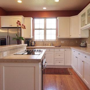 Idéer för ett klassiskt kök, med en nedsänkt diskho, luckor med infälld panel, vita skåp, kaklad bänkskiva, beige stänkskydd, stänkskydd i porslinskakel, rostfria vitvaror, mellanmörkt trägolv och en köksö