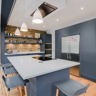This is an example of a medium sized contemporary l-shaped kitchen in London with flat-panel cabinets, composite countertops, white splashback, stainless steel appliances, an island, a submerged sink, blue cabinets, brick splashback, medium hardwood flooring, brown floors and white worktops.