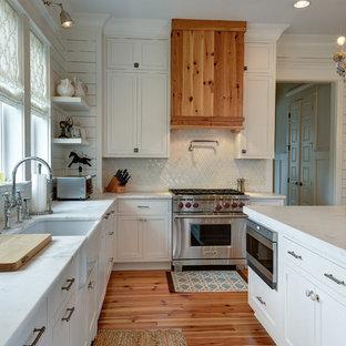 Klassische Küche in L-Form mit Landhausspüle, Schrankfronten im Shaker-Stil, weißen Schränken, Küchenrückwand in Weiß, Rückwand aus Mosaikfliesen und Elektrogeräten mit Frontblende in Charleston