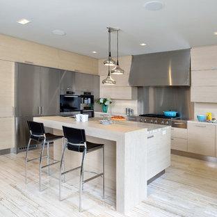 トロントの大きい北欧スタイルのおしゃれなキッチン (ドロップインシンク、フラットパネル扉のキャビネット、淡色木目調キャビネット、シルバーの調理設備の、ライムストーンの床、珪岩カウンター、ベージュキッチンパネル) の写真