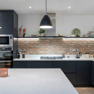 ダブリンのコンテンポラリースタイルのおしゃれなキッチン (フラットパネル扉のキャビネット、レンガのキッチンパネル、白いキッチンカウンター、アンダーカウンターシンク、ステンレスキャビネット) の写真