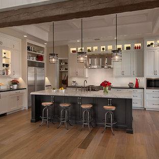 Klassische Küche mit Küchengeräten aus Edelstahl, weißen Schränken, Schrankfronten mit vertiefter Füllung und Küchenrückwand in Weiß in Phoenix