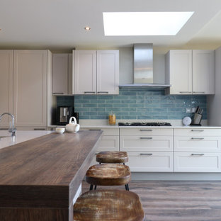 Design ideas for a large transitional l-shaped eat-in kitchen in London with a drop-in sink, shaker cabinets, quartzite benchtops, ceramic splashback, panelled appliances, with island, white benchtop, white cabinets, blue splashback, medium hardwood floors and brown floor.