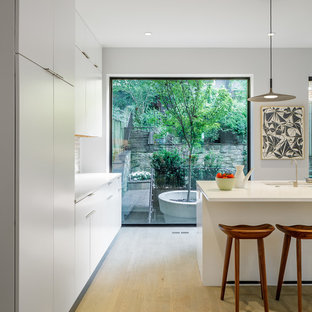 Design ideas for a mid-sized midcentury galley eat-in kitchen in DC Metro with an undermount sink, flat-panel cabinets, white cabinets, quartz benchtops, beige splashback, stone tile splashback, panelled appliances, light hardwood floors, with island, beige floor and yellow benchtop.