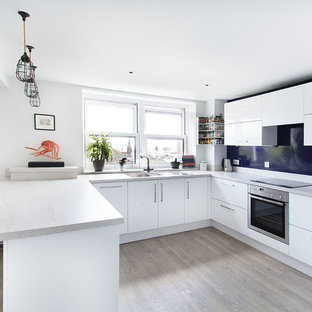 Inspiration for a contemporary u-shaped kitchen/diner in Buckinghamshire with a double-bowl sink, flat-panel cabinets, white cabinets, blue splashback, stainless steel appliances, light hardwood flooring and a breakfast bar.