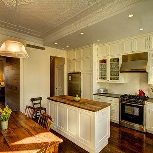ニューヨークのヴィクトリアン調のおしゃれなキッチン (シルバーの調理設備の、木材カウンター、アンダーカウンターシンク、シェーカースタイル扉のキャビネット、白いキャビネット、白いキッチンパネル、サブウェイタイルのキッチンパネル) の写真