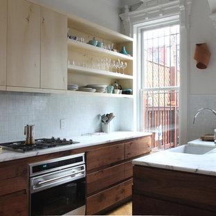 ニューヨークのコンテンポラリースタイルのおしゃれなキッチン (アンダーカウンターシンク、フラットパネル扉のキャビネット、淡色木目調キャビネット、白いキッチンパネル、モザイクタイルのキッチンパネル、パネルと同色の調理設備) の写真