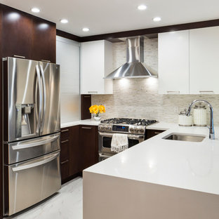 Inspiration for a mid-sized transitional u-shaped eat-in kitchen in New York with flat-panel cabinets, quartz benchtops, white splashback, mosaic tile splashback, stainless steel appliances, an undermount sink, white cabinets, marble floors and a peninsula.
