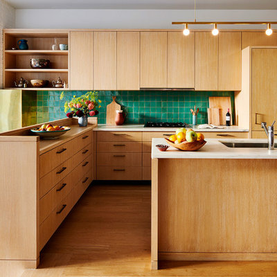 Mid-century modern u-shaped light wood floor and brown floor kitchen photo in New York with a drop-in sink, flat-panel cabinets, light wood cabinets, green backsplash and an island