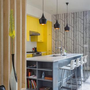 ニューヨークの大きい北欧スタイルのおしゃれなキッチン (ドロップインシンク、フラットパネル扉のキャビネット、黄色いキャビネット、人工大理石カウンター、白いキッチンパネル、サブウェイタイルのキッチンパネル、シルバーの調理設備の、濃色無垢フローリング、茶色い床、白いキッチンカウンター) の写真