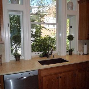 Immagine di una cucina ad U chic con lavello sottopiano, ante in stile shaker, ante in legno scuro, top in pietra calcarea, paraspruzzi in lastra di pietra e elettrodomestici in acciaio inossidabile