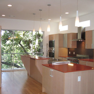 This is an example of a small modern galley open plan kitchen in Dallas with a double-bowl sink, flat-panel cabinets, light wood cabinets, quartz benchtops, brown splashback, mosaic tile splashback, stainless steel appliances, light hardwood floors, with island, beige floor and orange benchtop.