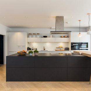Свежая идея для дизайна: кухня в современном стиле с плоскими фасадами, белыми фасадами, белым фартуком, черной техникой, светлым паркетным полом и островом - отличное фото интерьера