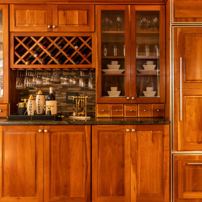 Example of a mid-sized eclectic u-shaped medium tone wood floor and brown floor open concept kitchen design in Other with a single-bowl sink, glass-front cabinets, medium tone wood cabinets, granite countertops, brown backsplash, matchstick tile backsplash, paneled appliances, a peninsula and green countertops