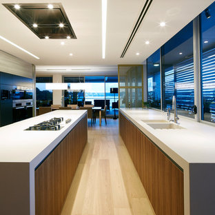 Photo of a modern galley kitchen in Sydney with an integrated sink, flat-panel cabinets, dark wood cabinets, concrete benchtops, window splashback, black appliances, light hardwood floors, with island, beige floor and grey benchtop.